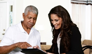 Man helping woman navigate electronic tablet