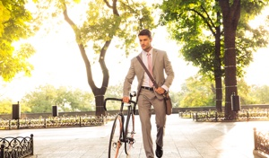 Man walking through a park with bicycle