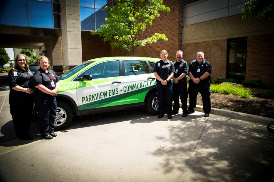 Paramedics posing around a car